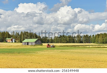 Small Harvester working in fields and harvests - stock photo