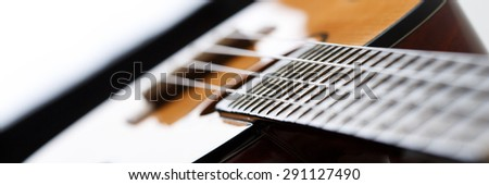 Small Hawaiian four stringed ukulele guitar body closeup letterbox view. Musical instruments shop or learning school concept