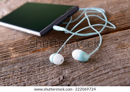 Small headphones with mobile phone on wooden desk - stock photo