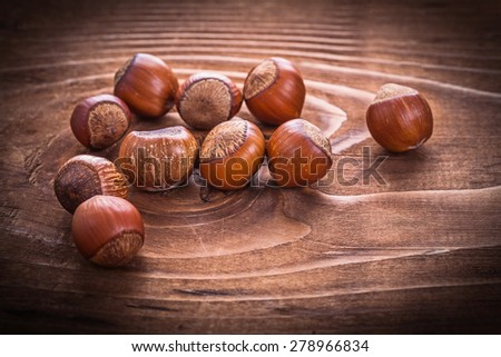 small heap of hazelnuts on vintage wooden board food and drink concept  - stock photo