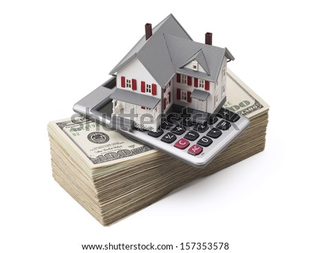 Small house and calculator sitting on a stack of hundred dollar bills against white background. Concept of real estate. Clipping path included.  - stock photo