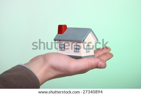 Small house in a hand on a green background