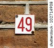 small house number forty-nine, red lettering  engraved in Formica - stock photo