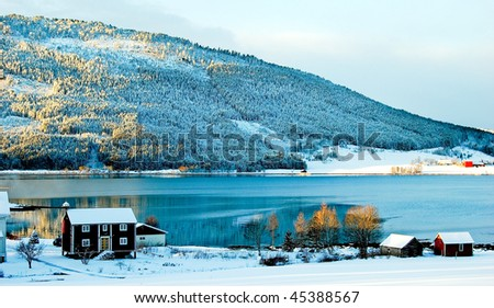 Small house onshore of fjord in Norway, winter - stock photo