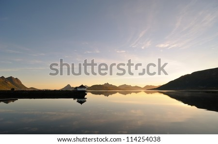 Small house reflected in the waters of the northern fjord at sun - stock photo