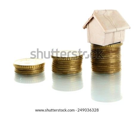 Small house standing on stack of coins isolated on white - stock photo