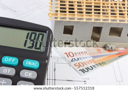 Small house under construction, calculator and currencies euro on electrical drawings for project, concept of building home cost