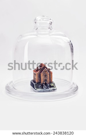 Small house under the protection of a glass cover. - stock photo