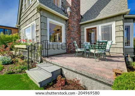 Small house with brick chimney. View of backyard walkout deck with patio table set - stock photo