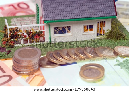 small house with euro coins and banknote / house - stock photo