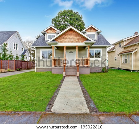 Small house with wooden column porch. View from walkway - stock photo
