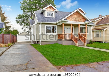 Small house with wooden column porch. View of garage and driveway - stock photo