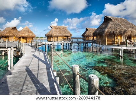 small houses on water in the ocean - stock photo
