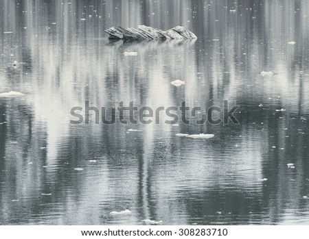 Small Ice formation and mountain reflection in water - stock photo