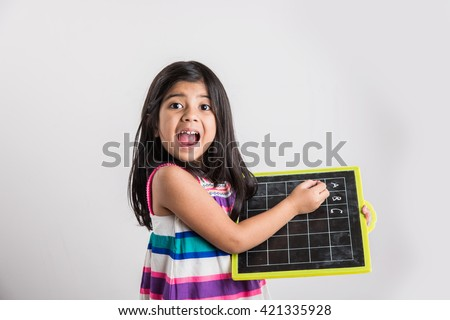 small indian girl excited while writing abc on black school slate board, over white background - stock photo