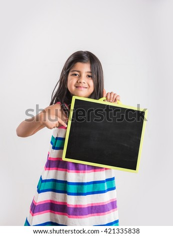 small indian girl holding and showing blank school slate, asian small girl with black school slate board - stock photo