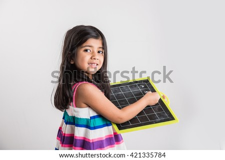 small indian girl writing abc on black school slate board, over white background - stock photo