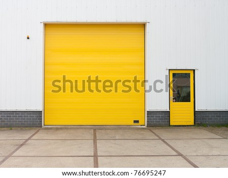 small industrial warehouse with a single yellow roller door - stock photo