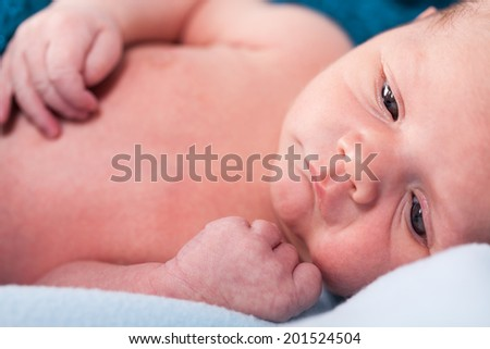 Small infant wrapped in knitted fabric lying on soft white bed