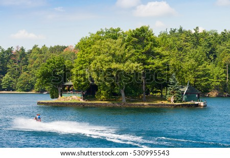 Small island and a couple on a fast jet ski