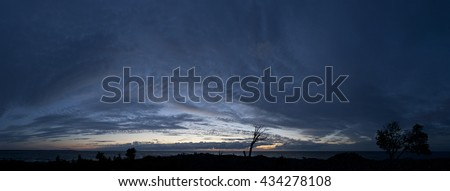 Small island in the Baltic Sea panorama. Single dead tree, sunset and stormy night on the beach. Mohni, Estonia, Europe. - stock photo