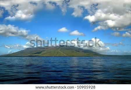 Small island in the Pacific ocean.  Vivid blue skies and reflection.