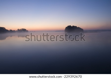 Small island over calm foggy lake water surface just before sunrise, Mazury, Poland - stock photo