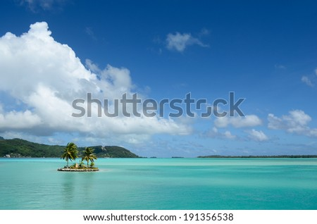 Small island with coconut palm trees in the clear water of the blue lagoon of Bora Bora island in the Tahiti archipelago French Polynesia. - stock photo