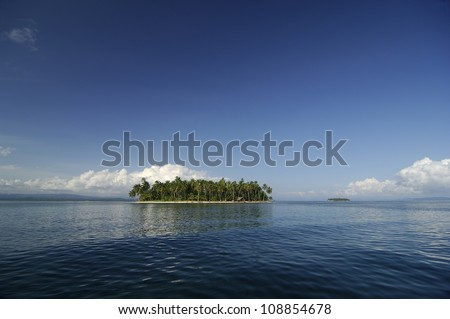 Small island with palm trees forest in middle of blue sea. Kuna Yala, San Blas Archipelago, Panama, Caribbean, Central America. - stock photo