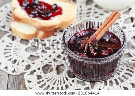 Small jam dish with cherry jam and delicious toast for breakfast and a jug of milk on wooden table, selective focus and place for text  - stock photo