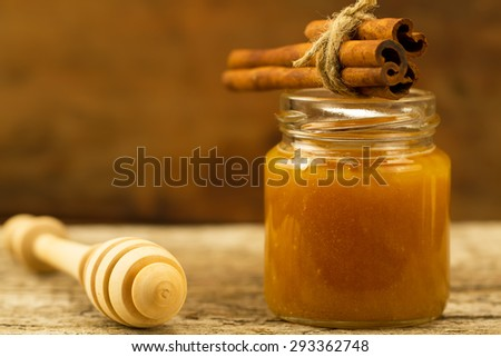 small jar of honey with drizzler and cinnamon on wooden background - stock photo