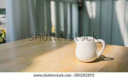 Small jar of milk on wooden table.