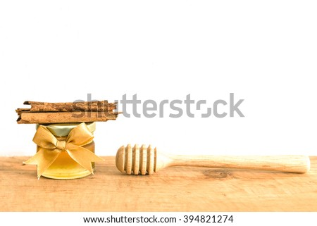 small jars of fresh honey with cinnamon  on wooden background - stock photo