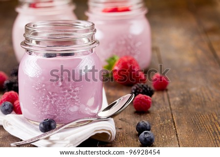 Small jars on wooden table with homemade yogurt with fresh berries - stock photo