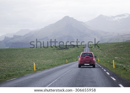 Small jeep driving on a road in rural settings towards mountains ahead. - stock photo