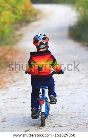 Small kid on his bike on winding road - stock photo