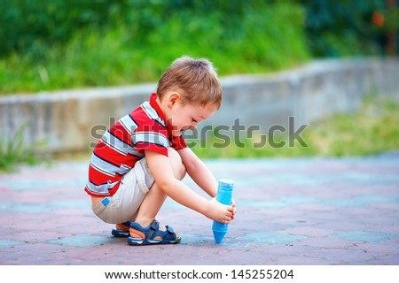 small kid painting the ground with chalk - stock photo
