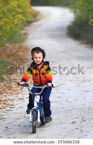 Small kid riding his bike on dirt road in the forest  - stock photo