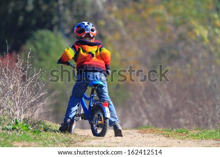 Small kid with his bike on dirt road - stock photo