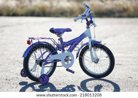 Small kids bike with training wheels outdoors. - stock photo