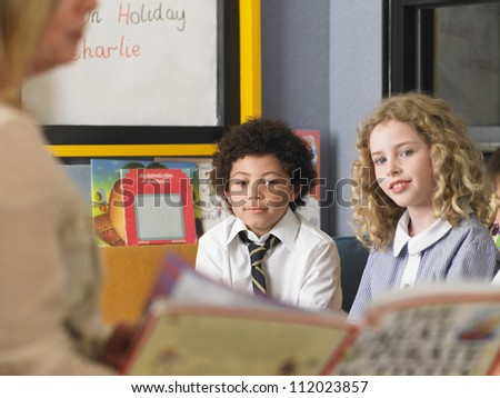 Small kids studying together in classroom with teacher