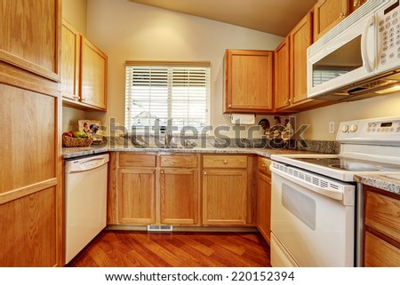 Small kitchen area with granite tops and white appliances - stock photo