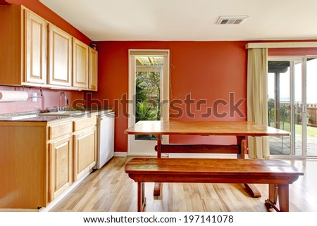 Small kitchen area with light tones cabinets , hardwood floor and bright red wall. View of rustic dining table with bench