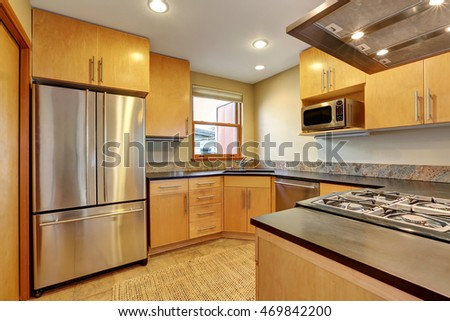 Small kitchen room interior with light brown cabinets and tile floor. Northwest, USA