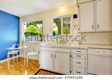 Small kitchen room interior with white cabinets, blue walls and glass dining table. Northwest, USA