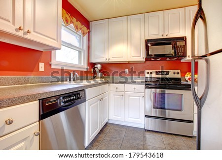 Small kitchen room with concrete tile floor, red walls, steel appliances and white wooden cabinets - stock photo