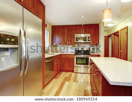 Small kitchen with hardwood floor, cherry cabinets and steel appliances.