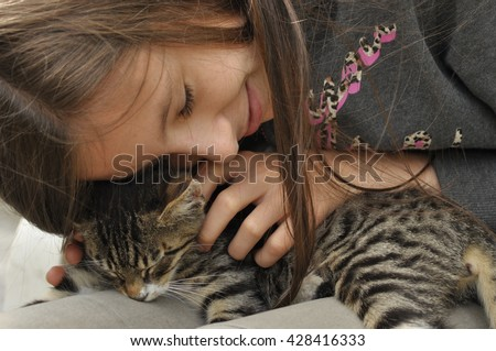 Small kitten sitting on a girl's lap. Stroking and hugging mascot, pet.