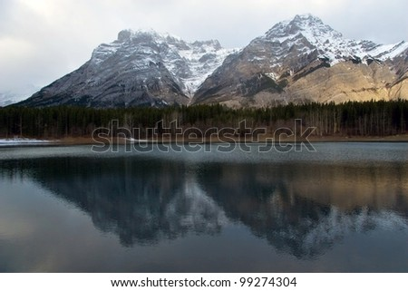 Small lake in Canadian Rockies, reflection of Peaks - stock photo