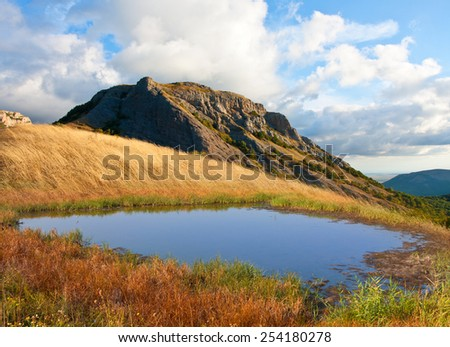 Small lake in mountains at nice autumn day - stock photo
